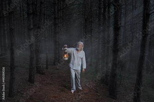 A vitiligo man with a kerosene lamp in the dark forest Fotobehang