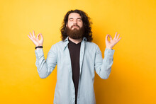 Bearded Young Man Relaxes During Meditation, Keeps Eyes Closed, Spreads Palms Sideways In Nirvana Over Yellow Background