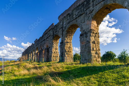 Tela Park of the Aqueducts Rome, the imposing arches of the Claudio with blue sky and clouds and shadows reflected on the lawn