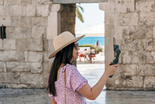 Side View Of Young Woman Using Gimbal And Mobile Phone In City.