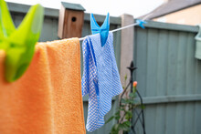 Multi Coloured Cleaning Clothes Seen Hanging Out To Dry On A Back Yard Washing Line.