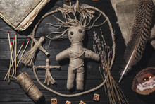 Female Voodoo Doll With Pins Surrounded By Ceremonial Items On Black Wooden Background, Flat Lay