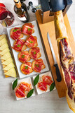 Fototapeta Zwierzęta - Spanish tapas and appetizers.Tapas and appetizers of Iberian ham with a glass of wine, ripe tomatoes and cow cheese on a white wooden background.