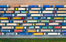 Aerial View Of Colorful Trucks In Terminal At Sunset In Summer. Top View Of Logistic Center. Heavy Industry. Transportation. Cargo Transport, Shipping. International Trucking. View From Drone Of Truck