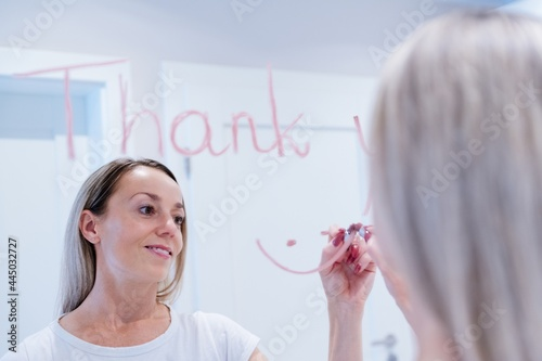 Fotografie, Obraz Blonde woman writes the word thank you on the mirror with a lipstick