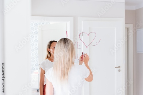 Fotografie, Obraz Blonde woman draws the inscription love and heart with lipstick on the mirror