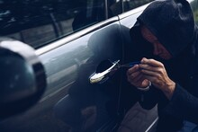 Car Thief Breaking Into Car With Picklock Or Screwdriver.