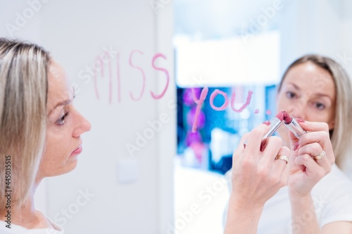 Fototapeta Blonde woman in white t-shirt writes the words I miss you on the mirror