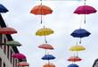 Vor blauem Himmel in Reihen hängende, bunte Regenschirme