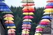 Lange Reihe mit vielen bunten Regenschirmen und Bäumen im Hintergrund