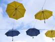 Vor blauem Himmel aufgespannte gelbe und blaue Regenschirme