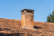 Roof With Tiles And Red Chimney In The Interior Of Brazil. In The Background Trees And Blue Sky.