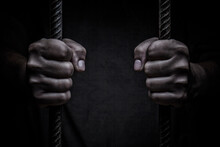 Closeup On Hands Of Man Sitting In Jail. Man Behind Jail Bars On Black Background