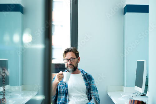 Obraz na plátně Mature man portrait looking on camera while drink coffee at office - freelance o