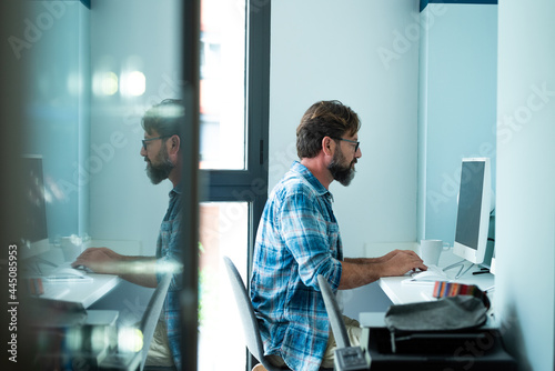 Obraz na plátně Bearded hipster style adult man working writing on desktop computer in office wo