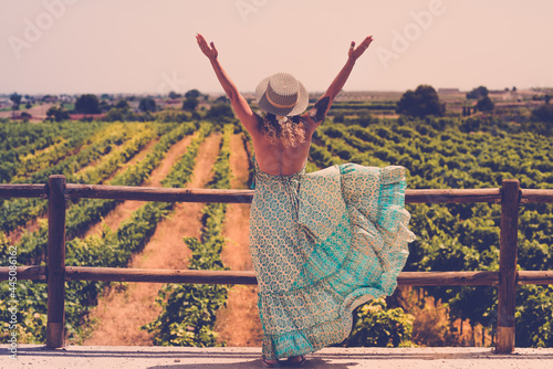Fototapeta Trendy boho chic style back of woman opening arms for freedom feeling in front o