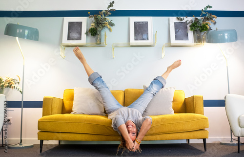 Fototapeta Happy and joyful adult woman lay down on the sofa in reverse position with legs