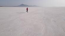 Aerial Shot Of An Asian Woman Jogging Across The Bonneville Salt Flats Flats In Utah