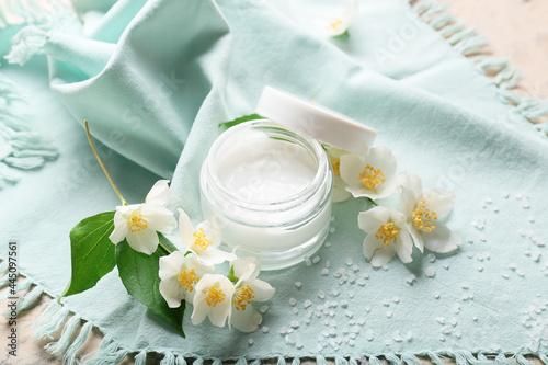 Fototapeta Composition with jar of cream and jasmine flowers on table