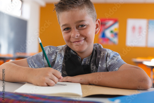 Fototapeta premium Portrait of smiling caucasian schoolboy with face mask sitting in classroom, writing in schoolbook