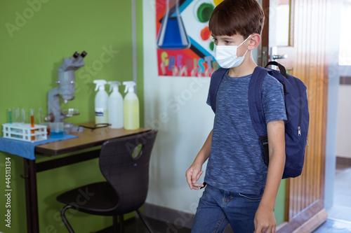 Fototapeta premium Caucasian schoolboy in classroom wearing face mask and schoolbag