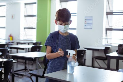 Fototapeta premium Caucasian schoolboy in classroom wearing face mask and schoolbag disinfecting hands