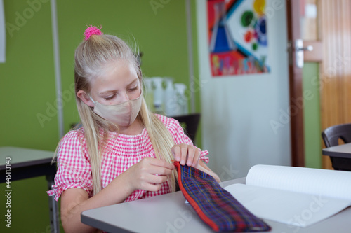 Fototapeta premium Caucasian schoolgirl sitting at desk in classroom wearing face mask