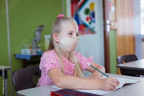 Fototapeta premium Caucasian schoolgirl sitting at desk in classroom wearing face mask during lesson