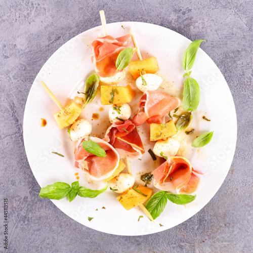 melon salad on stick with mozzarella and prosciutto ham