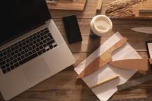 Laptop, Smartphone, Knife Molds And Other Utensils Lying On Desk At Knife Maker Workshop