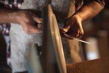 Hands Of Caucasian Male Knife Maker Wearing Apron, Making Knife In Workshop