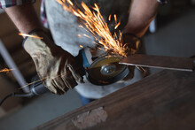 Hands Of Caucasian Male Knife Maker Wearing Apron, Using Angle Grinder In Workshop