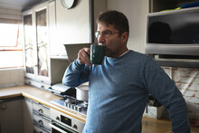Focused Caucasian Man Wearing Glasses, Standing In Kitchen Drinking Coffee