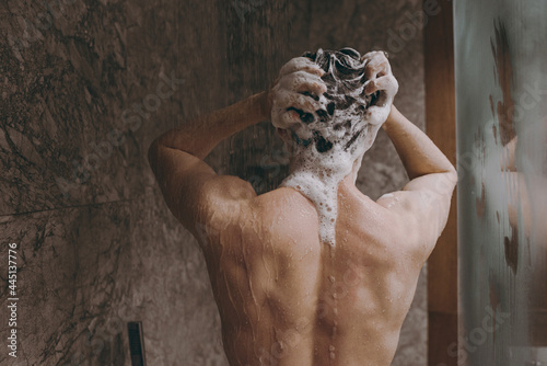 Back rear view young brunet half naked torso topless brunette man 20s taking hot shower wash hair with shampoo indoors in bathroom at home. People healthcare daily morning routine lifestyle concept