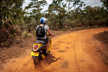 Tourist Travelling On A Scooter On A Tropical Island's Dirt Road
