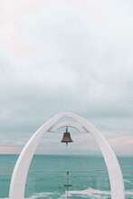 Closeup Of A Bell Hanging In An Arch Structure On A Beautiful Seascape Background
