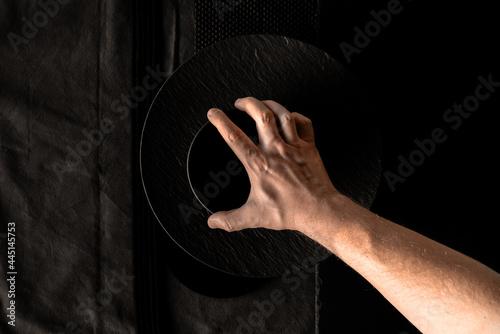 Fotografie, Obraz Hand hält schwarze Schüssel auf Teller auf schwarz strukturiertem Hintergrund