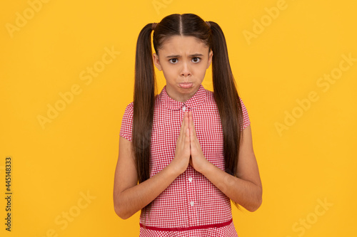 Fotografia Unhappy girl prayer plead holding palms together in prayer gesture yellow backgr