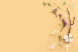 Top view image of flowers composition on pastel yellow background .Flat lay