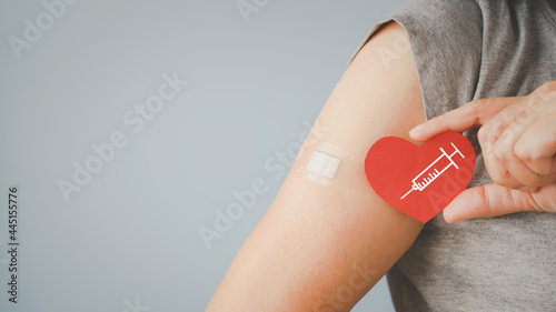 Fotografia senior woman holding red heart shape with  syringe and showing her arm with band