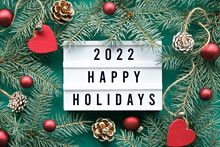 Light Board With Text 2022 Happy Holidays. Flat Lay With Fir Twigs And Xmas Decorations Around Light Box. Pine Cones, Red Wooden Hearts And Glass Baubles, Balls. Simple, Minimal Christmas Greeting