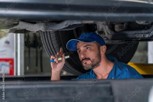 Murais de parede Car mechanic checking the car suspension