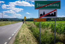Road Signs And Information Board Marking The End Of Build-up Area Of Strzegomiany Village, And Cycling Trail To Sulistrowice And Sulistrowiczki, Poland. A Woman With Backpack Walking Along The Road.