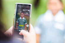 Mum Holding Mobile Phone To Take Photos Of Her Daughter On First Day Back To School