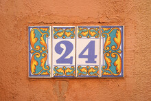 Decorated Ceramic Tiles 24 House Number On Orange Rough Wall