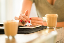 Close Up Photo Of A Woman's Hand With Red Nails Using Her Cellphone With Two Cups Of Coffee