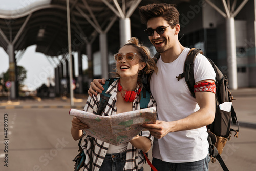Obraz na plátne Young joyful woman and brunette man hug and holds map