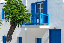 White Facade With A Blue Wooden Balcony And A Tree
