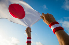Hands With Japan Red And White Wristband Holding A Japanese Flag Waving In Bright Sunny Blue Sky