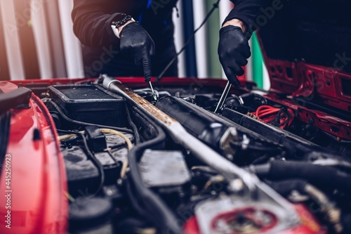 Fotografie, Obraz Car mechanic repairing customer engine with wrench. Car service